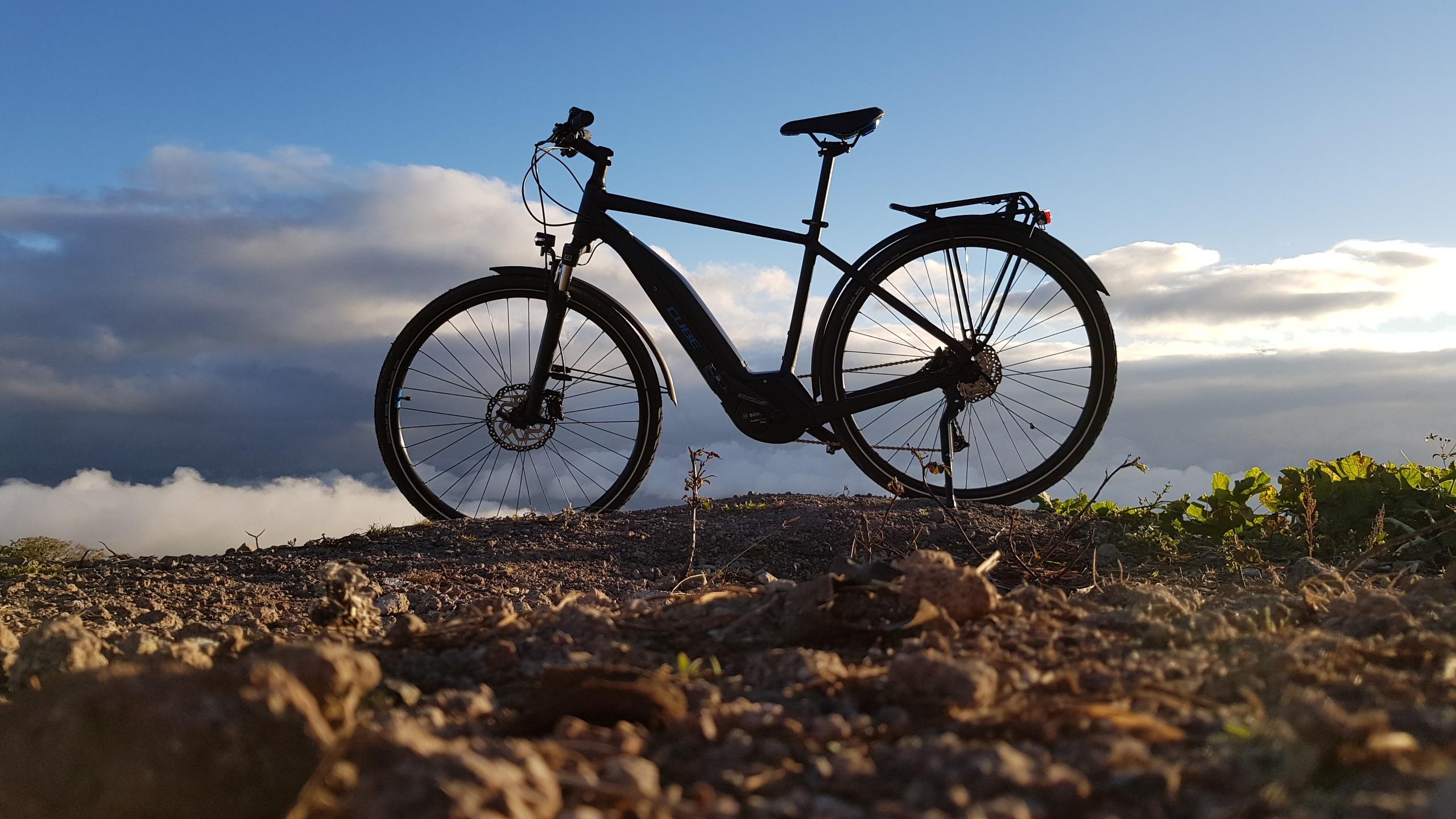 Bicicleta eléctrica Cube sobre un terreno en Tierra Blanca de Cartago. Al fondo se observan las nubes y el cielo despejado al atardecer. Fotografía: Osvaldo Calderón